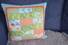 "A very useful way to practice your free motion quilting skills is to try them out on cushion covers! Marie Elisabeth Vaughan from Shark's Dinner made this lovely cushion with Good Fortune by Kate Spain for Moda Fabrics United Notions. ""I decided to quilt a grid in the centre simply following the seams using an Aurifil 50wt (5006), do some pebbling on the orange border with some #Aurifil 40wt (2150) and a leaf pattern in the blue border with my favourite variegated Aurifil 40wt (4654)."""