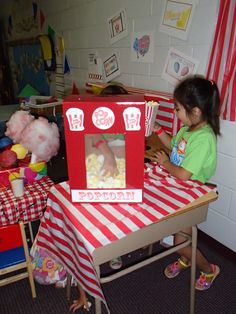 """""""Popcorn Machine"""" in Kinder Room """"Cotton Candy Cafe"""" play center at FBC Friendswood.  Popcorn machine is made from a box, spray painted red.  Holes were cut out for the """"windows"""" and covered with clear contact paper (2 sheets stuck together to make a window). Decals were found online.  Popcorn is packing peanuts lightly spray painted yellow.  The kids used the """"machine"""" along with the popcorn containers you can buy from the dollar store to serve each other pretend popcorn."""