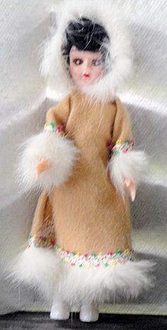 Atlantic-Richfield Oil Co. 7.5 inch hard plastic Eskimo nationality doll has a brunette mohair wig, moving brown eyes, a moving head, moving arms, and stationary legs. She is dressed in  her original well-made, but stapled on costume. It includes a long tan hooded flannel coat dress edged with color braid and white fur, and white boots. This doll was part of a set of 12 doll in colorful international costumes that were given as service station premiums in the later 1950s or early 1960s. ...