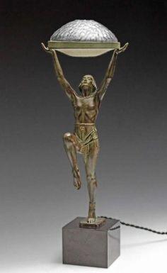Élégante grande sculpture éclairante Art Déco (H: 62 cm) vers 1925 signé M. LE VERRIER & cachet de fondeur à Paris. Rare grand modèle à structure en fonte d'art, alliage spécifique réalisé par Le Verrier à patine vert bronze à l'Antique, figurant une danseuse orientale partiellement dénudée seulement vêtue autour de la taille d'un drapé orné de passementeries rehaussées à l'or, elle tient dans ses bras tendus une coupole en verre à décor en réserve de fleurs & fruits joliment stylisés Art…