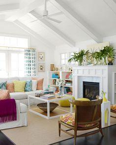 déco salon blanc - coussins multicolores, rideaux blancs à pois bleus, plantes vertes et poufs jaunes