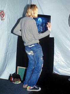 """Kurt Cobain playing air guitar backstage while Lenny Kravitz performed """"Are You Gonna Go My Way"""" at the 1993 MTV Music Awards."""