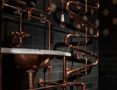 Black tiles create a neutral backdrop that lets the copper fixtures stand out.