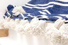 Cotton blanket, rug, throw, bedding with gorgeous pom poms, 100% natural and handmade in Morocco.   Designed by Berber Looms and handcrafted by local artisans on traditional wooden looms using 100% quality cotton.   Available in 15 stunning colours, these chic, lightweight blankets are perfect throughout the year.   Colour: Marine Blue & Pure White. Material: 100% cotton  Choose from a selection of three sizes, they can be used as a bedspread for your bed, a throw for the living room or for…