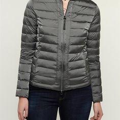 WOOLRICH W'S UL SUNDANCE GRIJS Dames. Een heerlijke jas voor de lente van het merk Woolrich. De jas is kort van model en is licht gewatteerd. In het midden is een rits verwerkt met aan weerszijden een jaszak met ritssluiting.