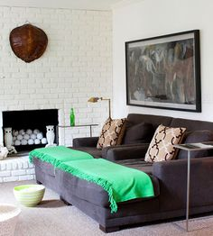 Comfortable lounging sofa, white brick fireplace, big art, whimsical owls.    Brick Makeover