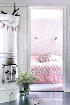 Makuuhuoneen pastellinen tunnelma syntyi tapetin sävyistä. Marika löysi samettisen päiväpeitteen H&M Homen mallistosta. Sen päällä on vanha pitsipeite, kirpparilöytö sekin.