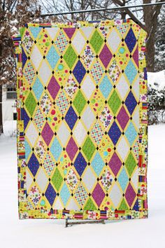 this diamond lattice quilt looks like a window pane, but it also reminds me of a harlequin jester's outfit