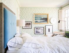 An asymmetrical grouping of landscapes keeps a delicate floral wallpaper from looking too sweet. domino.com