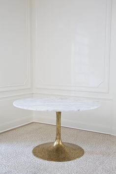 "KELLY WEARSTLER | IRIS DINING TABLE. This simple, tulip-style occasional table matches a solid white Carrara marble top with a gold leafed metal base. The leafed base features an antiqued finish and a dramatic taper. At 48"" in diameter, this table can function either in an entryway or as seating for four. The marble slab top is hand selected."