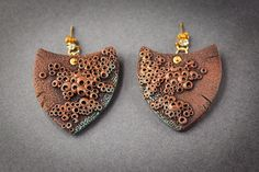 These earrings were inspired by ethnical and tribal ornaments and are made in a shape of a boat or a shield. They have a lovely brown colour combination with beautiful turquoise patina and embellished with golden elements. These earrings could be perfect for every day, cosplay parties and summer time. Size: 4x4cm (clay part) Gold plated earring studs with swarovski crystal.