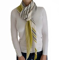 Oliena is a grey and white asymmetrical scarf with a yellow accent color made out of a 100 % alpaca yarn. Its' shaped in a way so that the stripes will appear in two different directions when it's wrapped around someone's neck which gives the scarf a very interesting look.