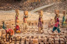 Carrying Bricks:  women carry recently fired bricks from the oven - by Mahadev Rojas, Venezuelan