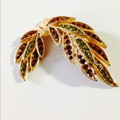"""Vtg Signed Trifari Crown Brooch  This brooch is a leaf motif in bronze and green rhinestones """"tied"""" together with a golden bow. It is signed, Trifari Crown ! Photos simply don't do this one justice!! Measures approximately 2"""" across and 2 1/4"""" in length! ✅ REASONABLE OFFERS WELCOME✅ NO LOWBALL OFFERS PLEASE  Rare find!! Thanks for stopping by my closet  Vintage Jewelry Brooches"""
