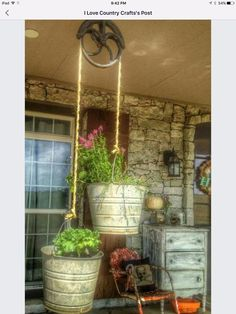 Use antique pulley and galvanized buckets for unique hanging planters
