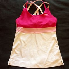 Nike workout tank with criss cross straps Super cute Nike tank with criss cross straps. The colors are hot pink, light pink and white. Built in bra. I wore this a handful of times but realized I'm not comfortable with the built in bra feature. There is a small stain on front that may come out with some stain removal, see last photo. Nike Tops Tank Tops