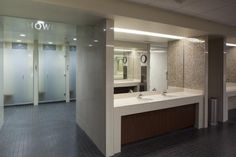 In the locker rooms, each shower stall was increased in size and full glass doors were added for more privacy. Vanity areas have solid-surface tops and aprons. Artisan glass mosaics were added to the interior of the vanity areas. Commercial Design, Commercial Interiors, Locker Room Bathroom, Spa Design, House Design, Shower Doors, Shower Stalls, Restroom Design, Public Bathrooms