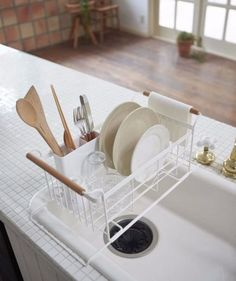 Utilize Over-the-Sink Space | A typical dish rack has a tendency to monopolize counter space, but this clever Tosca dish drainer rack floats above your kitchen sink, freeing up the counter and letting the drying dishes drip right into the sink. The combination of wood handles and white metal gives this rack a minimalist look, making it the most stylish dish rack we've ever seen.