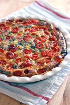 This easy, crustless quiche is packed with spinach and feta and tastes a lot like spanakopita. Topped with the MOST AMAZING slow roasted tomatoes!