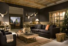 modern chalet interior | European mount taxidermy contrasted against the dark gray walls, stumps as bunch coffee tables.