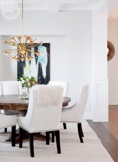 Mixing styles—In the dining room, Tanya likes the juxtaposition of the modern Sputnik-inspired chandelier with the traditional coffered ceiling. The artwork was a DIY project Tanya and Jure painted together on her 30th birthday.