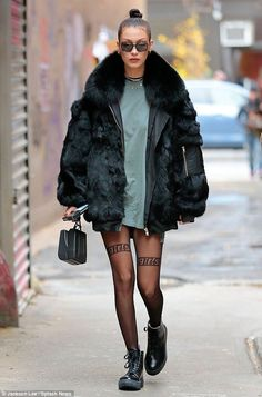 Cosy from the top up: It was a chilly Sunday morning in New York and model Bella Hadid wrapped up warm in a huge fur jacket that she wore over a grey T-shirt...and very little else
