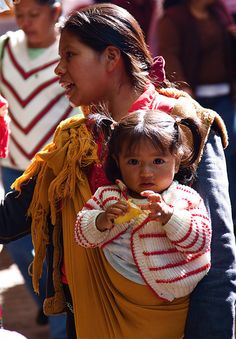 Toddler girl with pigtails being carried by her mother in a sling. Mexico