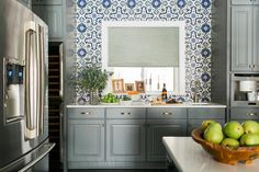 Blue and gray kitchen features gray raised panel cabinets adorned with brushed brass hardware paired with white quartz countertops and a blue Mediterranean style mosaic tile backsplash, Fireclay Grandola Tile, that goes up to the cieling.