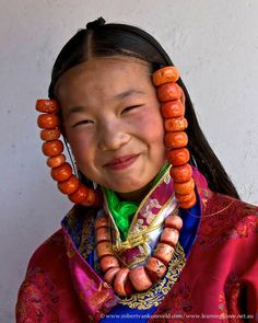 Tibet-2 24 Laru Mountain God Festivals  A delightful smile from a younger dancer wearing the very heavy coral neck and head pieces.