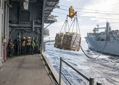 Sailors assigned to amphibious assault ship USS Bonhomme Richard (LHD 6) receive cargo from Military Sealift Command (MSC) dry cargo and ammunition ship USNS Carl Brashear (T-AKE 7) during an underway replenishment at sea.