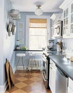 The pastel blue and white make this small kitchen feel open and spacious. Modern features like the wall mounted pot rack, retro stools, and stainless steel accessories go well with the vintage cabinets and checkered cork tile floor.