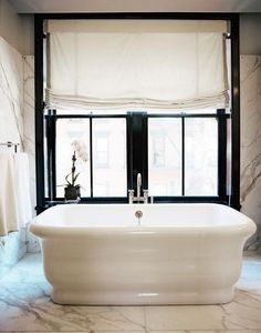 Bathroom - A white freestanding tub beside a window in a marble bathroom, large roman shade