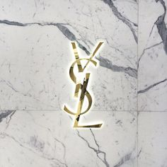 YSL logo in brass on carrara marble close up detail
