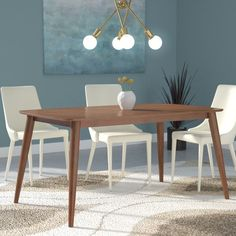 Boasting chic streamlined design with a Scandinavian influence, this dapper dining table lends mid-century modern appeal to any dining arrangement. Made from solid rubberwood in a rich woodgrain finish, this charismatic design features a gently bowed rectangular tabletop with smooth, curved corners and four long, tapered round legs. To create an understated ensemble in your open concept eat-in kitchen, start by rolling out a geometric cube repeat area rug for an intriguing pop of pattern…