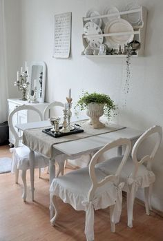 All vintage white shabby chic dinning area with a wall shelving system.