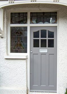 1930's External front door with sidelight door frame. Wing window sidelight door frames were used lots in the 1930's. This sidelight frame also has a transom with panes above the door and side. The door glass is a simple obscure glass complementing the decorative wooden glazing bar. This 1930's external front door has an elegant curve at the head of the door, six glazing apertures and three flat recessed panels.