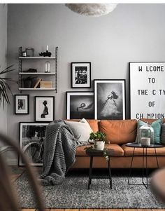 Coordination.. muted hues without being boring. Leather mid century sofa, soft grey wall, misty green velvet. Love.