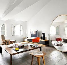 In this living room, a gigantic round floor mirror proves that size does indeed matter: The large scale of the mirror means it functions as a piece of furniture, and it also instantly doubles the...