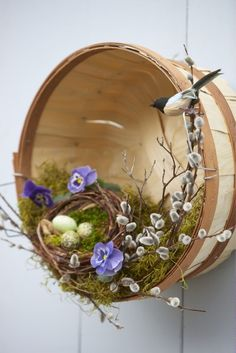 Inside a wooden, roujnd basket,  place birds , .nest, pussy willows line the along one side of the inside of the box, fake eggs,