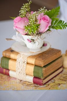 Recycle the old and antique books with tea cups by using them as a centerpiece. A simple flower arrangement with books and a tea cup is yet another unique concept  Source: www.everafterguide.com