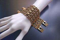 TB43 AG – Antique Gold Finish – Bracelet. Limited Edition. This bracelet has a stunning custom made screws design as an elegant feature. The 24K Antique Gold finish mesh has holes to let some of the skin visible. This item involves hours of meticulous work that gives an exquisite refined touch on this sumptuous statement. Handmade.