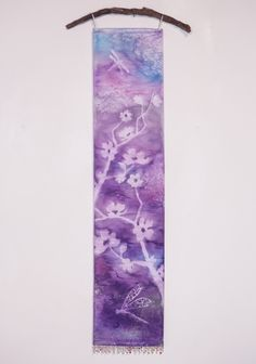 "Purple Blue Cherry Blossoms and Dragonflies Wall Art Tapestry. Misty nature silhouettes float over vibrant, watercolor hues in this unique hanging Art Panel. It is hand painted using a textile pigment on silky fabric, resulting in a subtle texture and shimmer. It measures 8"" x 36"", a long narrow painting perfect for small spaces. Delicate loops of ribbon allow it to be hung on a decorative rod or branch, while beaded fringe at the bottom adds a bit of sparkle and weight for a nice drape...."