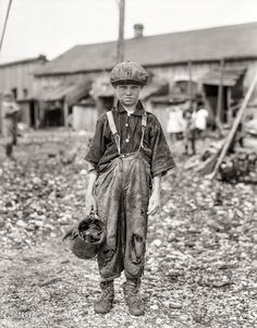 "Raggedy Henry: February 1912. ""Henry, 10-year-old oyster shucker who does five pots of oysters a day. Works before school, after school, and Saturdays. Been working three years. Maggioni Canning Co., Port Royal, South Carolina."" Glass negative by Lewis Wickes Hine"