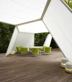tente de jardin par Paola Lenti avec un coin repas table ovale et chaises vertes