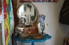 A paint dipped table holds glass jars filled with bracelets, a mirror, and a vintage bust wearing a favorite necklace.  What a fun way to display jewelry. | Dream Accessory Closet by Janeane Pittman Interior Design