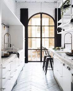 Der Fensterrahmen mit den Vorhängen inszeniert die Küche und den Blick nach außen