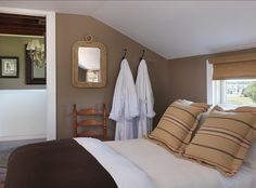 bamboo blinds, white and brown bedding, taupe walls, striped shams