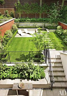 The manicured rear garden of a London townhouse features two limestone terraces.