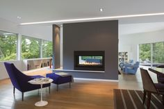 Open space with big windows and a fireplace in the middle.