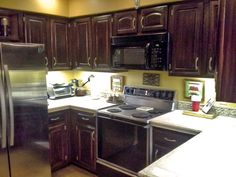 """Marvelous kitchen makeover by Melynda Crocker Bounds; """"I wanted to show you some before and after pictures of my kitchen... I used General Finishes Java Gel Stain, and I love my new cabinets. Instead of buying new hardware for the doors, I spray painted them with Krylon flat metallic silver. My entire kitchen makeover cost me around $100.00. I LOVE General Finishes!!"""" What a great job, and a lot of savings! Thanks for sharing, Melynda."""